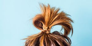 Close-Up Of Woman With Hair Bun Against Blue Background