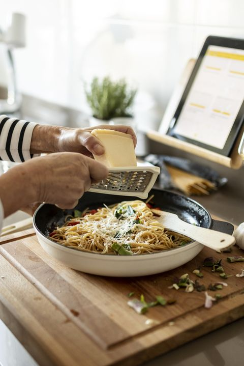 close up of woman with tablet cooking pasta dish in kitchen at home