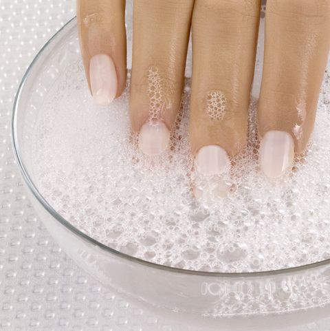 Close up of woman's hand in bowl of soapy water