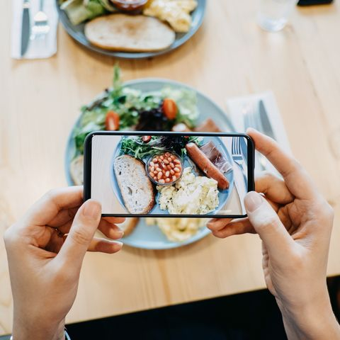 close up of woman's hand taking a photo of fresh breakfast with smartphone