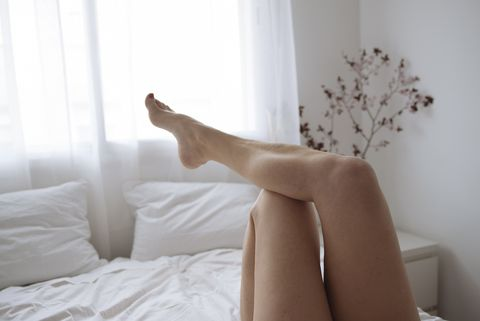 close up of wome's legs lying on bed in white bedroom