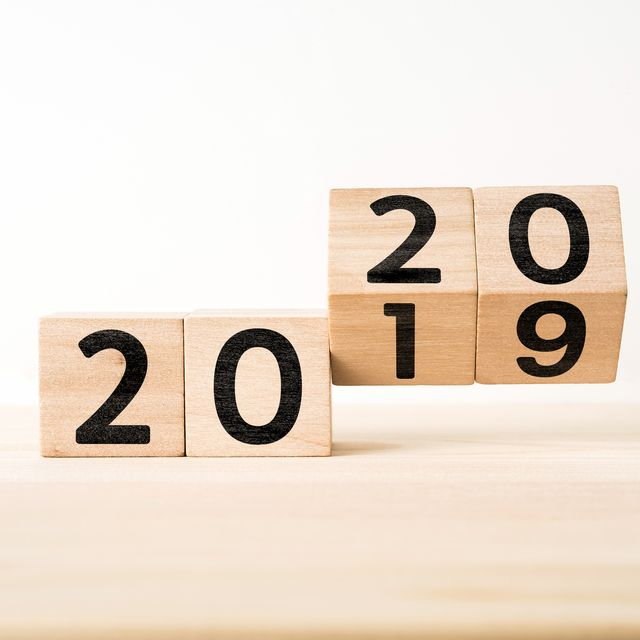 Close-Up Of Wooden Blocks With 2019 2020 Number On Table Against White Background
