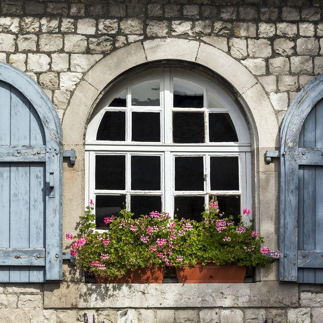 Close-up of wooden shutters on an arched window on a stone building with flower boxes
