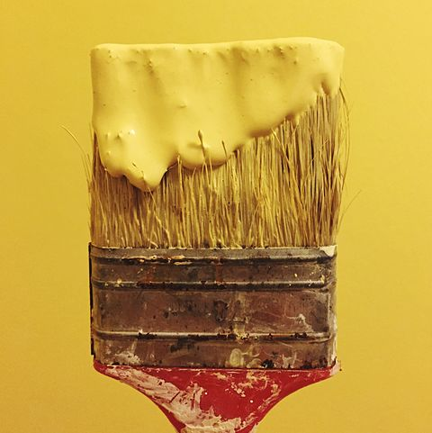 Close-Up Of Yellow Paint On Brush Against Wall
