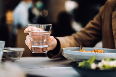 close up of young asian woman drinking a glass of water while having meal in a restaurant healthy lifestyle and stay hydrated