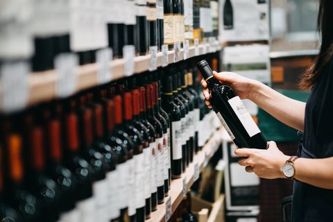close up of young asian woman walking through supermarket aisle and choosing a bottle of red wine from the shelf in a supermarket