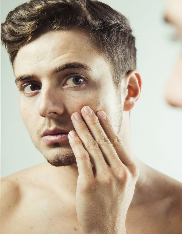 Close-up of young man looking at reflection in bathroom mirror, studio shot