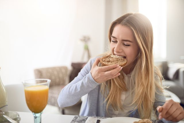 close up of young woman eating breakfast at home