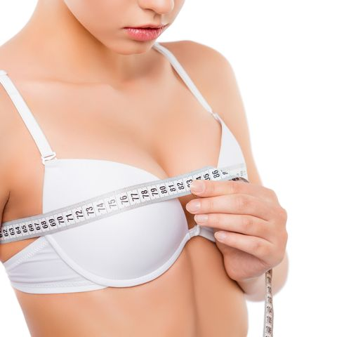 close up of young woman measuring her bust size with tape measure
