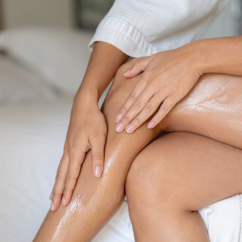 close up on a woman applying cream on her legs