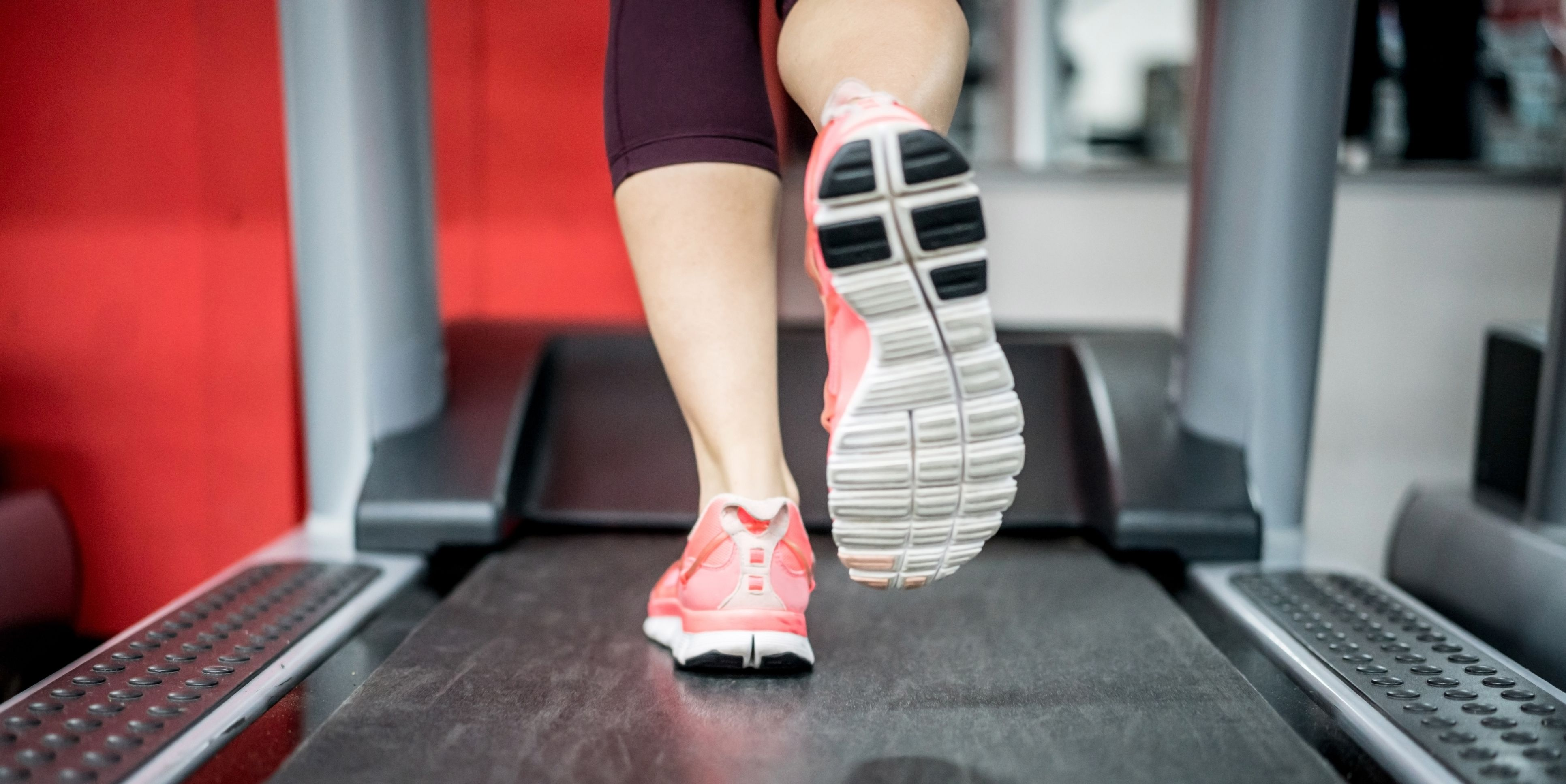 Close-up on a woman running on the treadmill at the gym