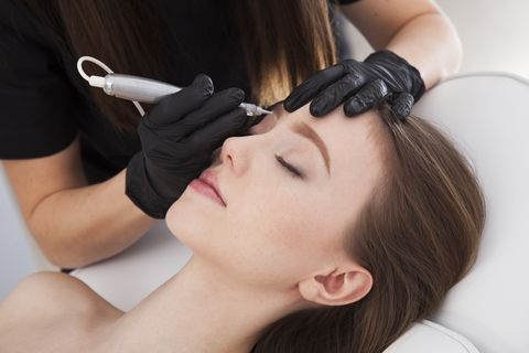 Close up on beautician doing permanent make up of eyebrows.