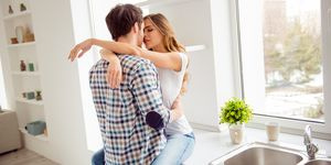 Close up photo pair beautiful he him his macho she her lady just married overjoyed hold each other hands bonding hugging touch lips going kiss desire apartments flat bright kitchen room indoors