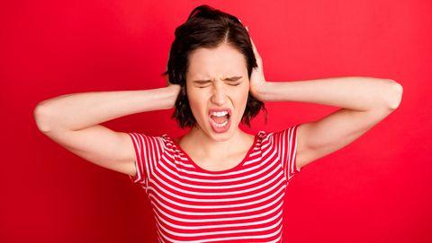 vrouw houdt oren dicht en schreeuwt