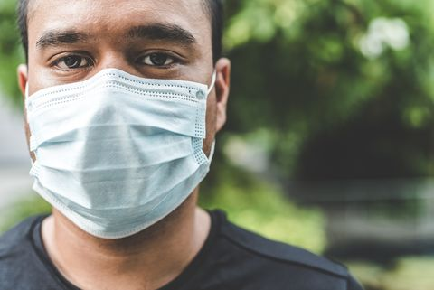Close-up portrait of man wearing pollution mask while standing against trees