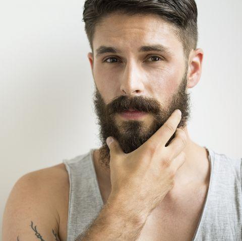 Close up portrait of serious man rubbing beard