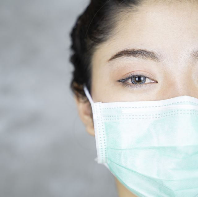 close up portrait of young asian woman with medicine health care mask against grey room background