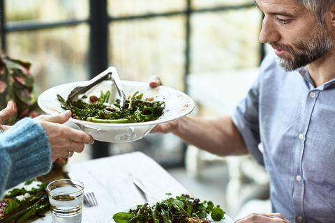 Close up shot of mature man being served fresh salad