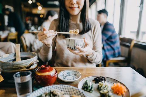 close up shot of smiling young woman enjoying japanese cuisine with various side dishes, miso soup and green tea in restaurant