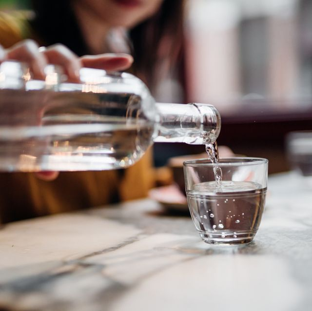 close up shot of woman pouring water into glass at restaurant