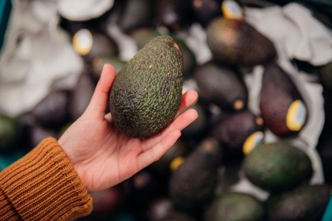 close up shot of woman's hand holding avocado in grocery store