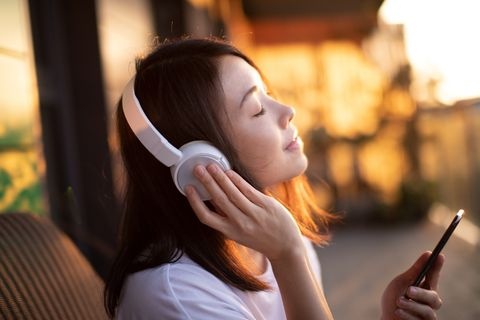 close up shot of young woman enjoying music over headphones and using smart phone
