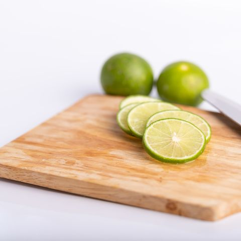 close up sliced of the green lime and seed with a knife place on wooden board in a kitchen on white