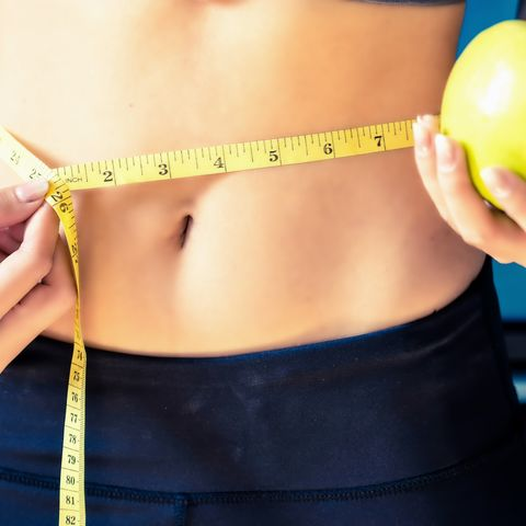 Close up Slim young woman measuring her waist with a tape measure.Healthy lifestyle, Diet Nutrition Concept.
