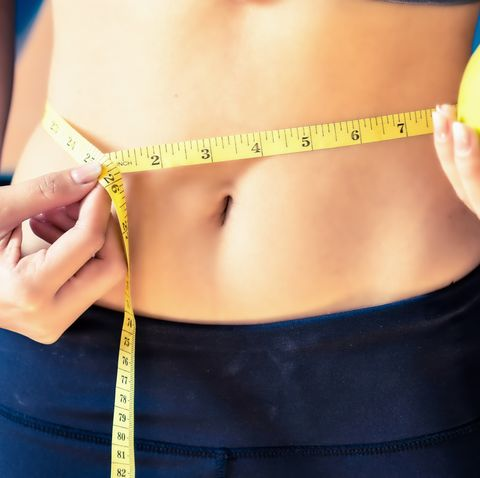 close up slim young woman measuring her waist with a tape measurehealthy lifestyle, diet nutrition concept