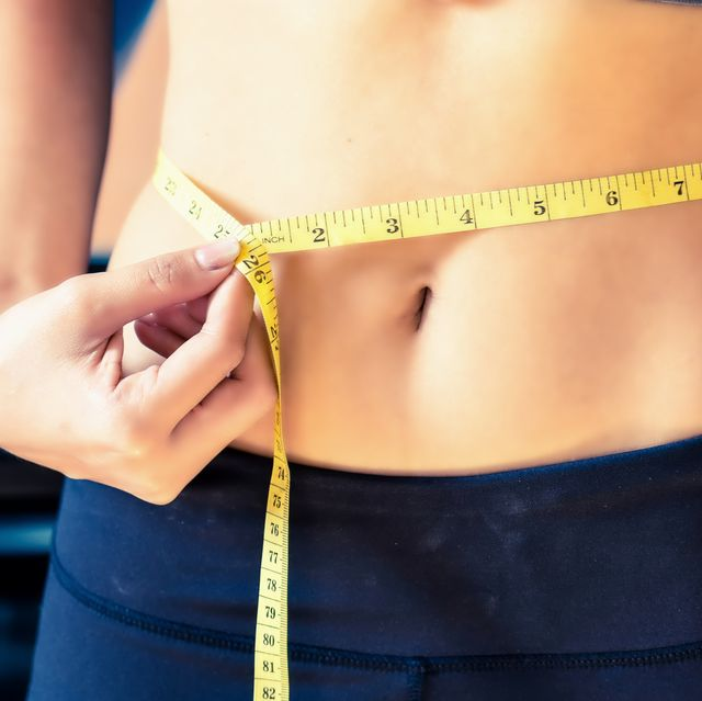 close up slim young woman measuring her waist with a tape measure healthy lifestyle, diet nutrition concept