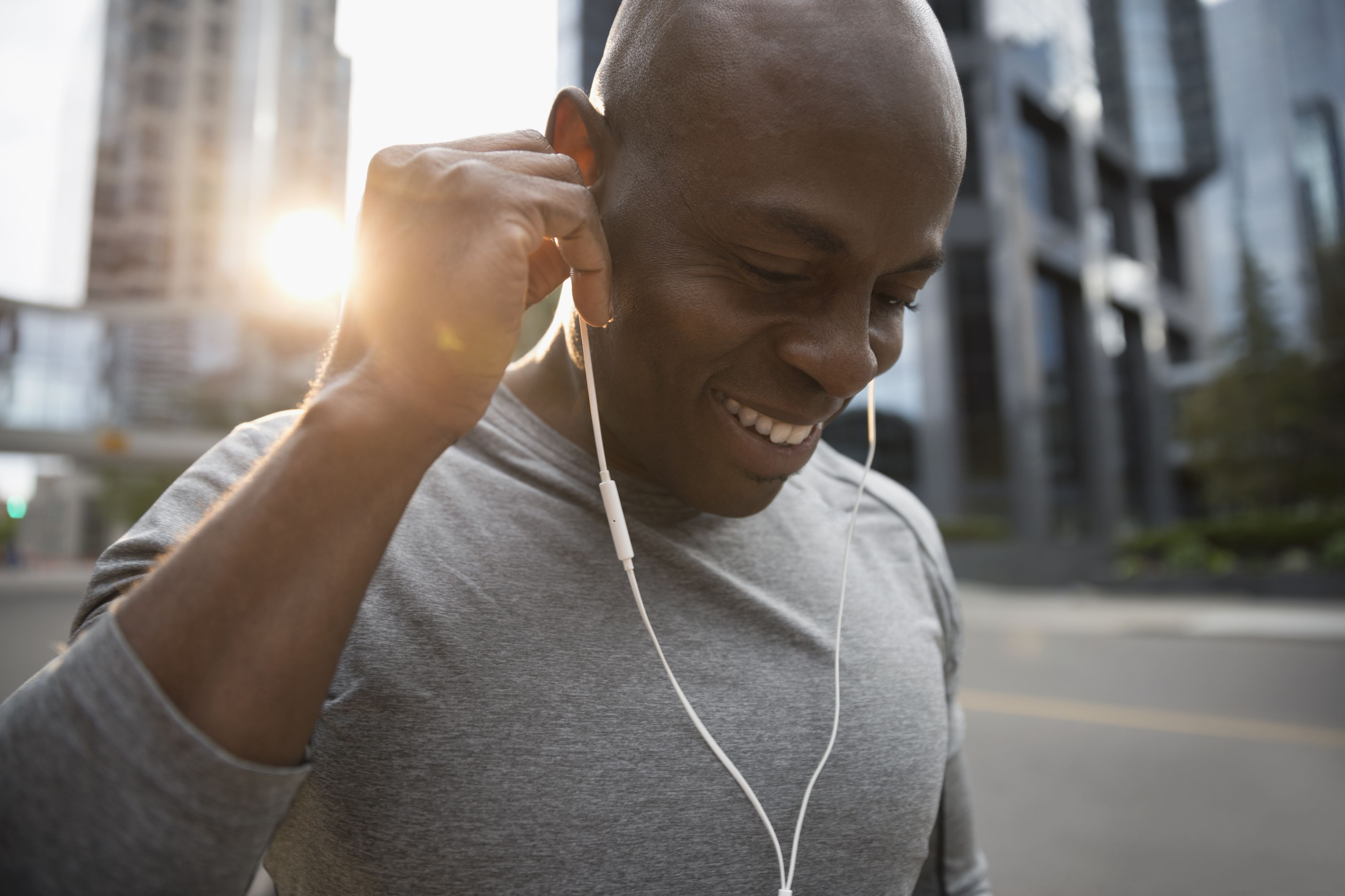 Close up smiling male runner listening to music with earbud headphones on urban street