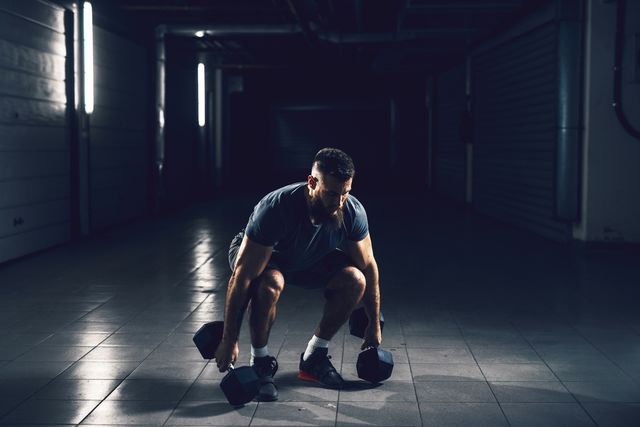 close up view of focussed hardworking active fitness strong muscular bearded bodybuilder man crouching before raising heavyweight dumbbell in the underground garage or urban gym while looking far away