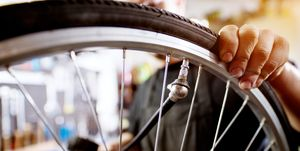 Close up view of man's hand pumping bicycle wheel with air and checking pressure.