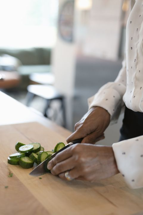 Close up woman cooking, cutting vegetables in kitchen
