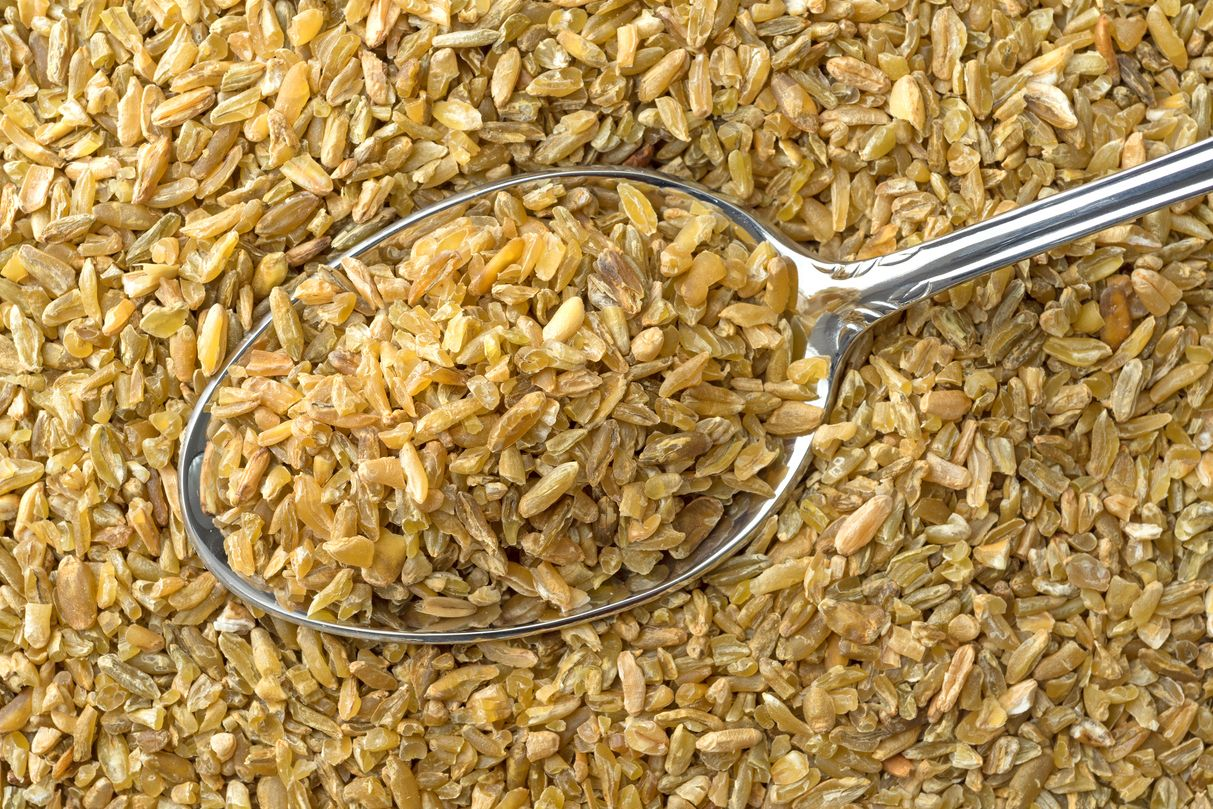 Close view of cracked freekeh grain with spoon