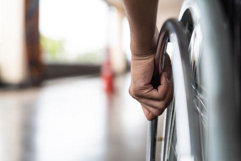 closeup disabled man hand on wheel of wheelchair