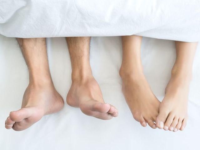 Closeup Feet of couple man and woman making love or sex on bed under blanket at hotel, home, sweet valentine concept.