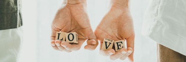 Closeup of couple hand holding the LOVE letters and  be hand in hand together. Romantic and sweet valentine concept. Forever love.