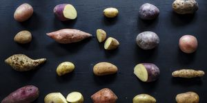 Closeup of fresh various organic potatoes on black background