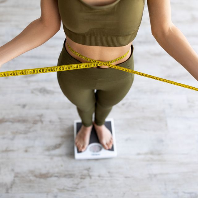 closeup of indian female measuring waist, standing on scales, checking weight loss result, measuring body parameters