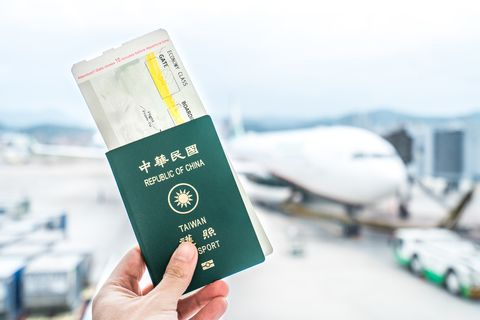 closeup of man holding taiwan passport and boarding pass at airport