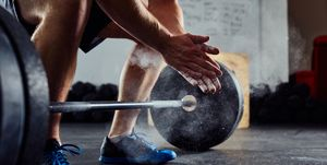 Closeup of weightlifter clapping hands before  barbell workout a