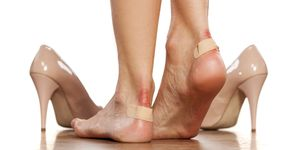 Closeup of  women's heels with a blister plaster on