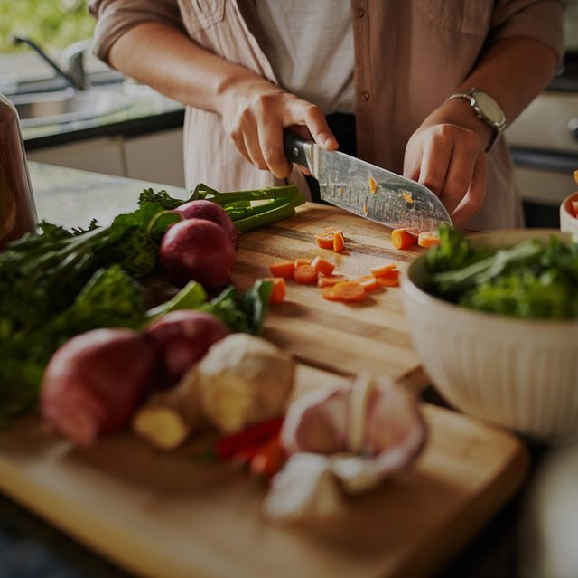 closeup of young female hands chopping fresh vegetables on chopping board while in modern kitchen preparing a healthy meal to boost immune system and fight off coronavirus