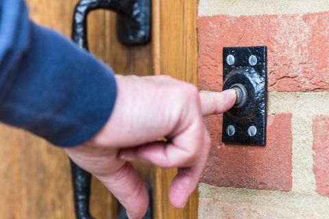 Gros plan sur une main en appuyant sur un bouton de sonnette de porte