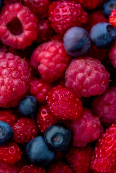 Closeup photo of fresh colorful mix of berries: blueberry, raspberry and wild strawberry