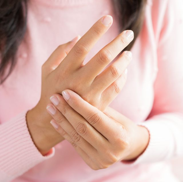Closeup woman sitting on sofa holds her wrist hand injury, feeling pain. Health care and medical concept.