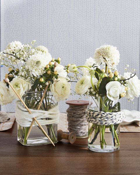 plain glass vases wrapped with strands of yarn and knitting needles