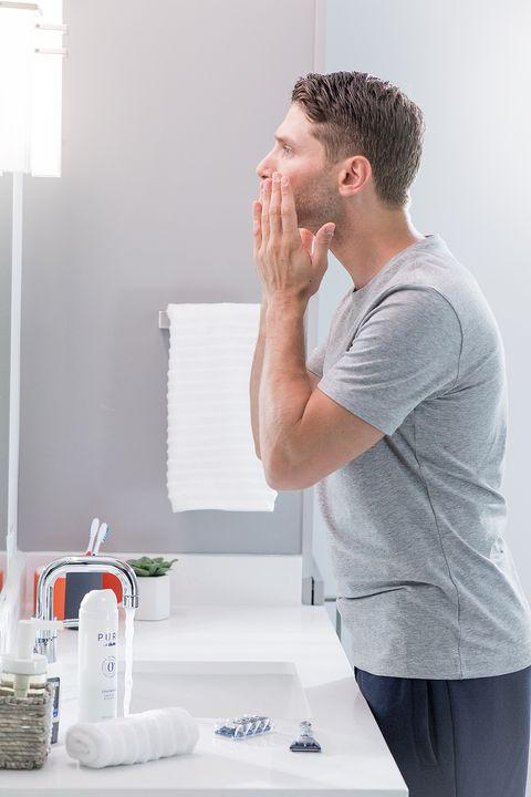 un hombre joven frente al espejo se prepara para afeitarse con productos skinguard de gillette