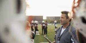Coach with clipboard talking to teenage boy high school football team on football field